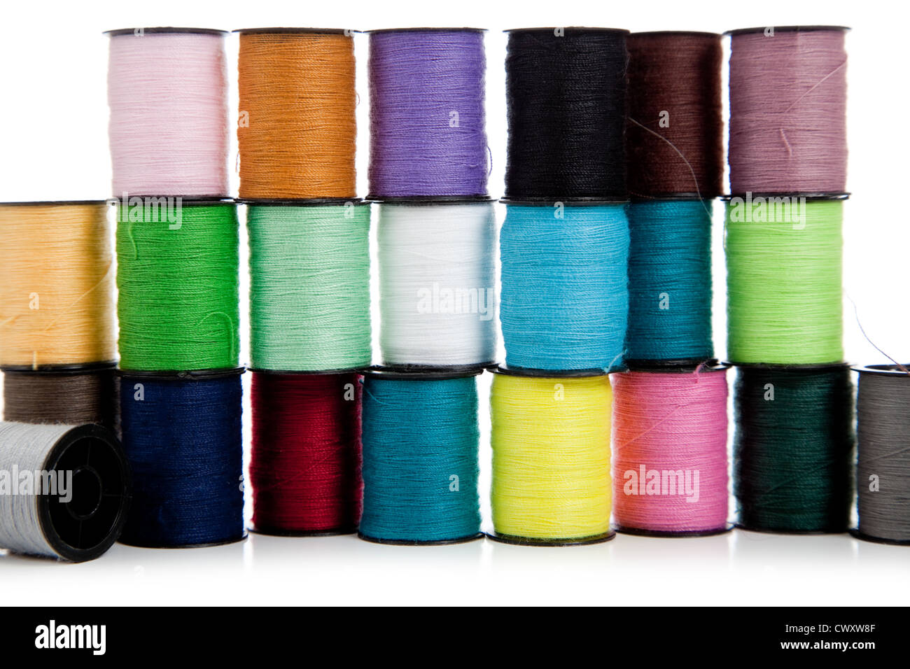 Assorted colored spools of thread on a white background - Stock Image