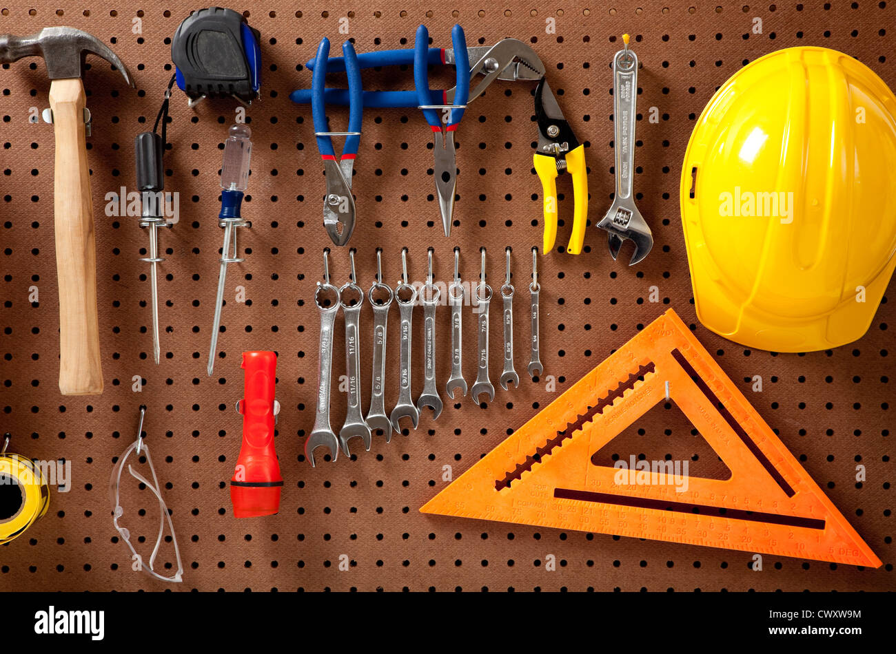 A pegboard with various tools such as: hammer,  wrenches, flashlight, screwdrivers - Stock Image