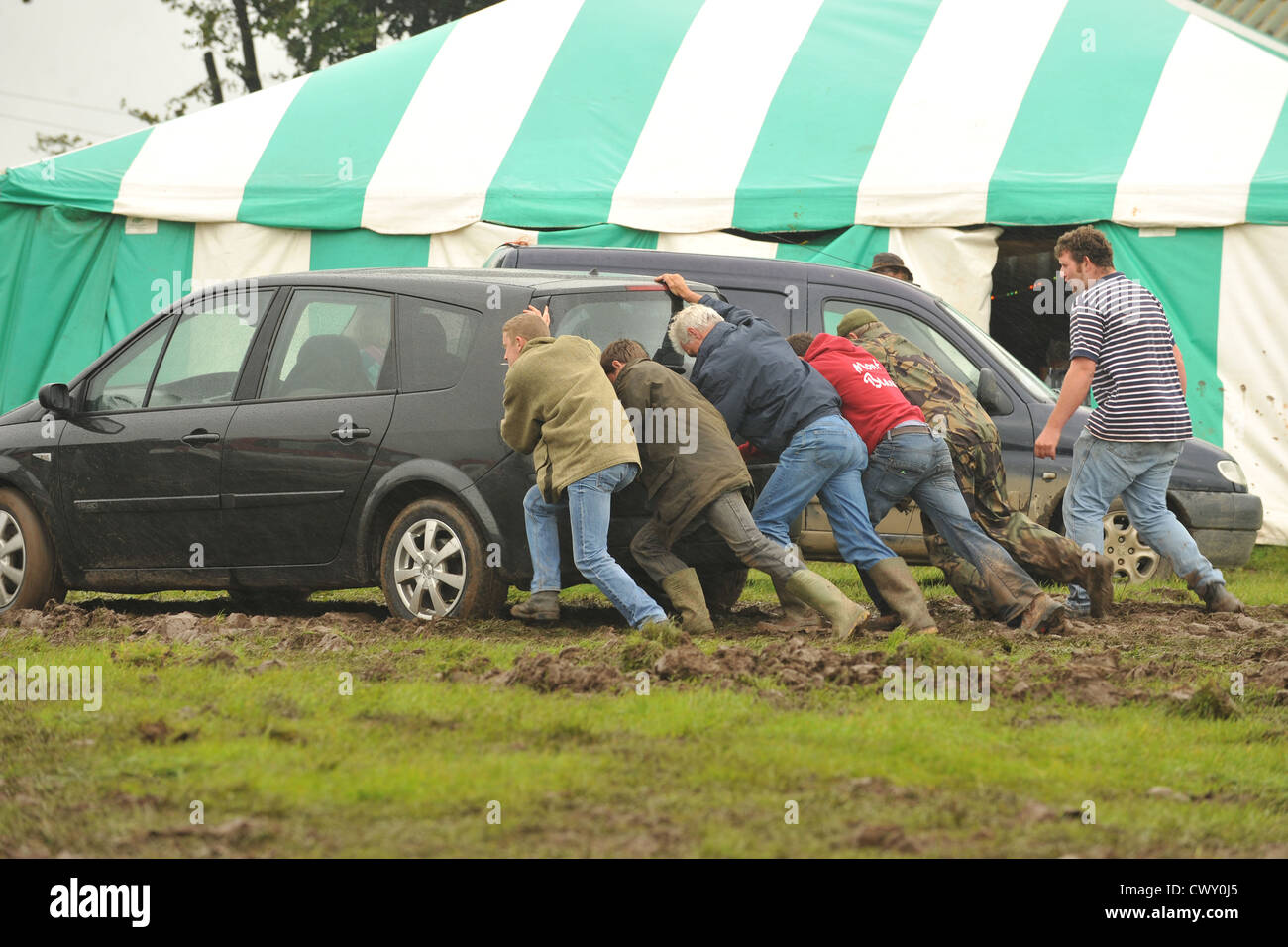 pushing a car stuck in mud Stock Photo