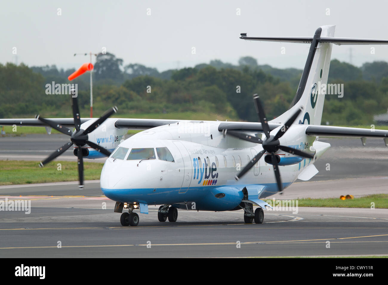 A Flybe Bombardier Dash 8 taxiing on the runway of Manchester International Airport (Editorial use only) - Stock Image