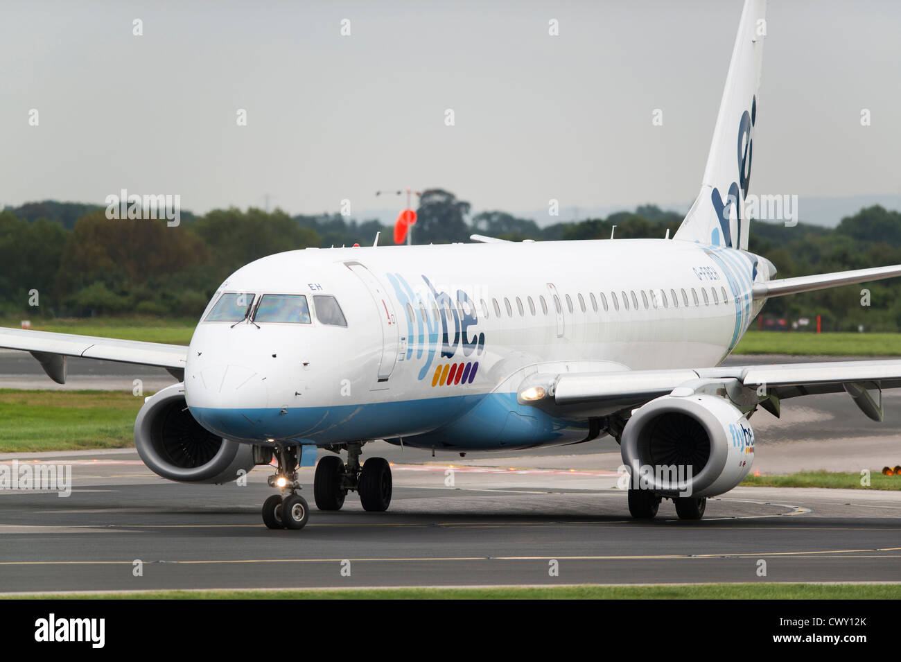 A Flybe Embraer 190 taxiing on the runway of Manchester International Airport (Editorial use only) - Stock Image