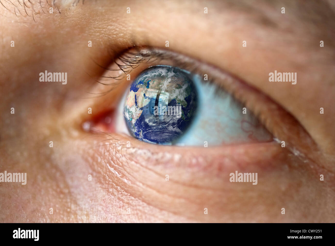Close-Up of a male face with the earth in the eye - Stock Image