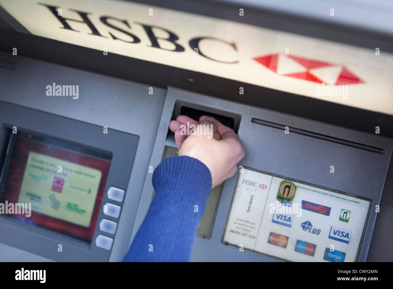 Women inserting a debit card into a hsbc cash point to withdraw money - Stock Image