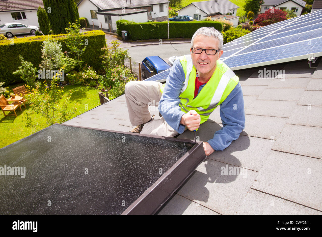A workman fitting solar thermal panels for heating water, to a house roof in Ambleside, Cumbria, UK, - Stock Image