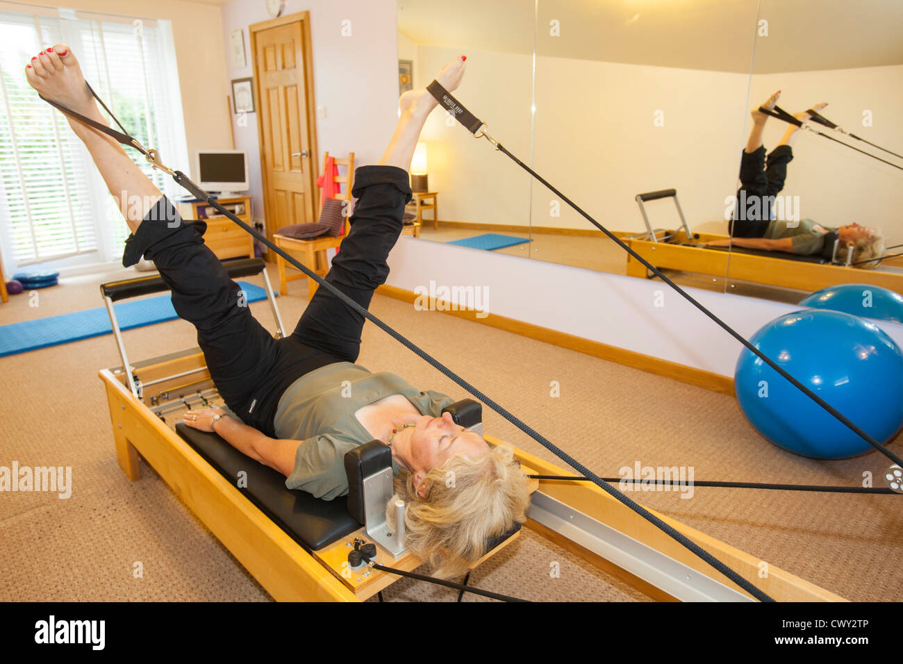A Pilates instructor using a pilates reformer machine. - Stock Image