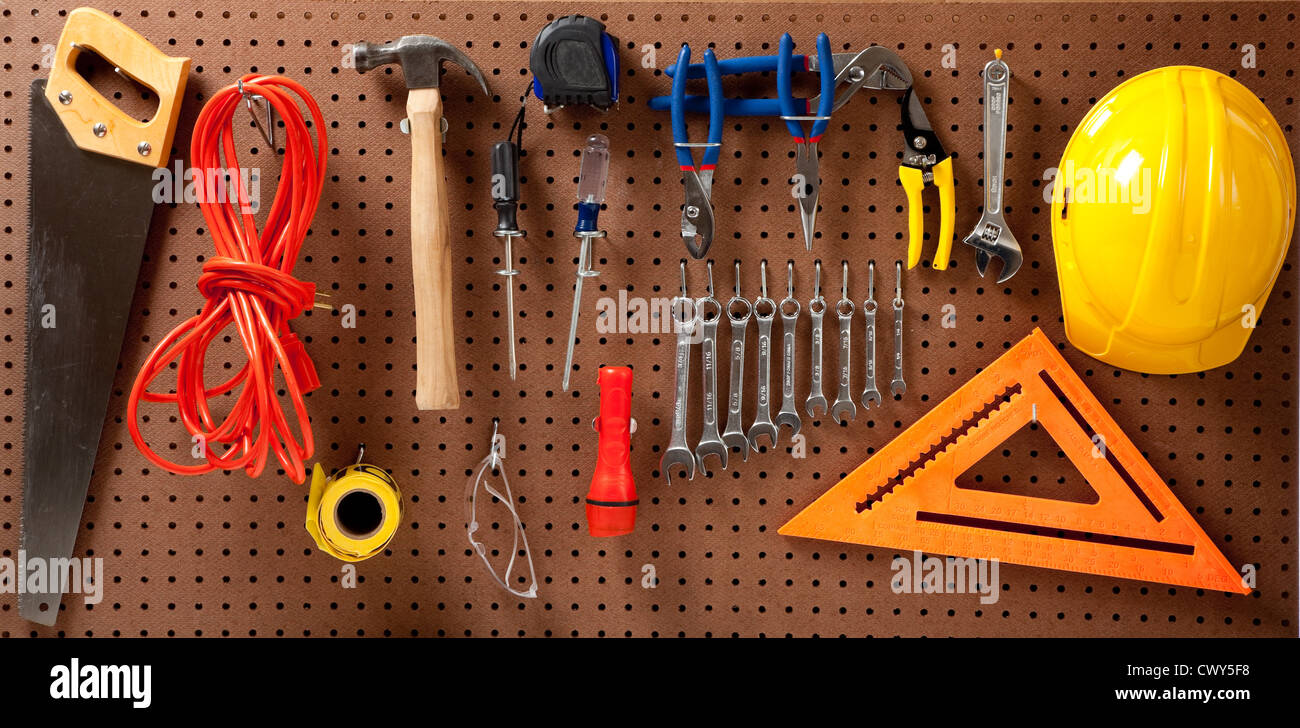 A pegboard with various tools such as: hammer, saw, wrenches, flashlight, extension cord, screwdrivers - Stock Image