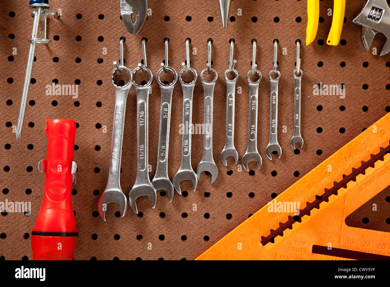 a peg board with assorted wrenches and various tools - Stock Image