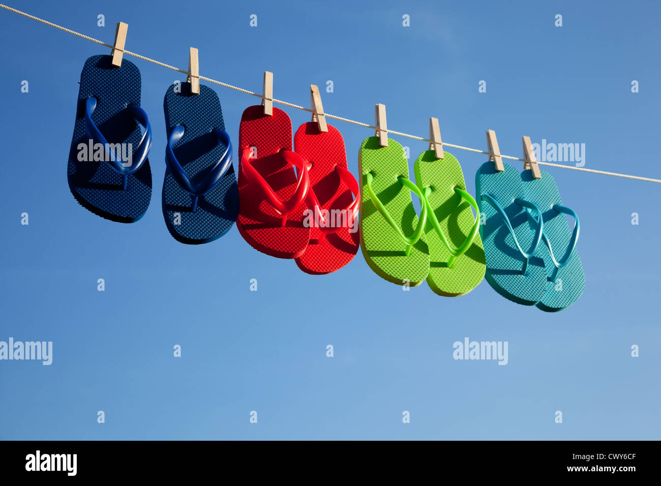 2cd8b4e30720a4 A row of various colored flipflops on a clothesline on a sky blue background