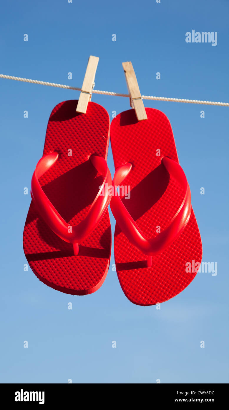 c9490057fafbf6 A pair of bright red flipflops on a clothesline with a sky blue background