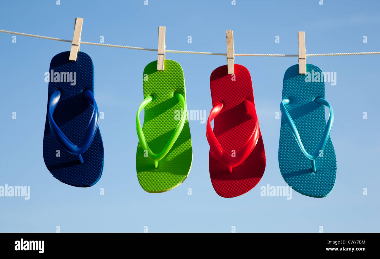 3506009f8e0f29 Assorted colored flipflops on a clothesline with a sky blue background