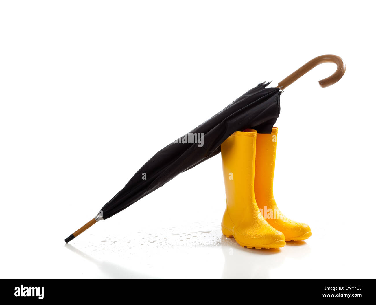 A pair of yellow rainboots and a black umbrella on a white background with copy space - Stock Image