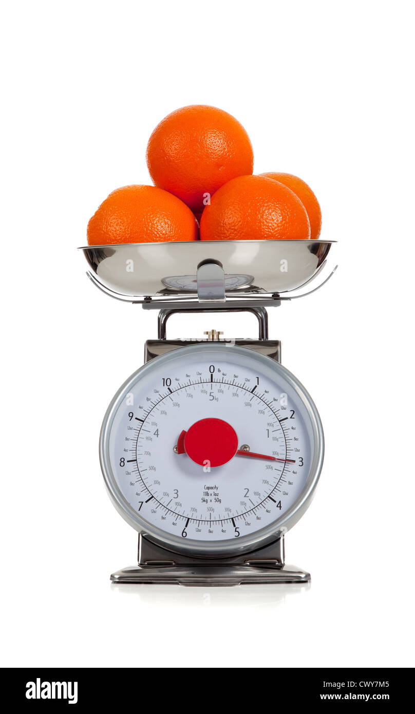 oranges on a food scale and a white background - Stock Image