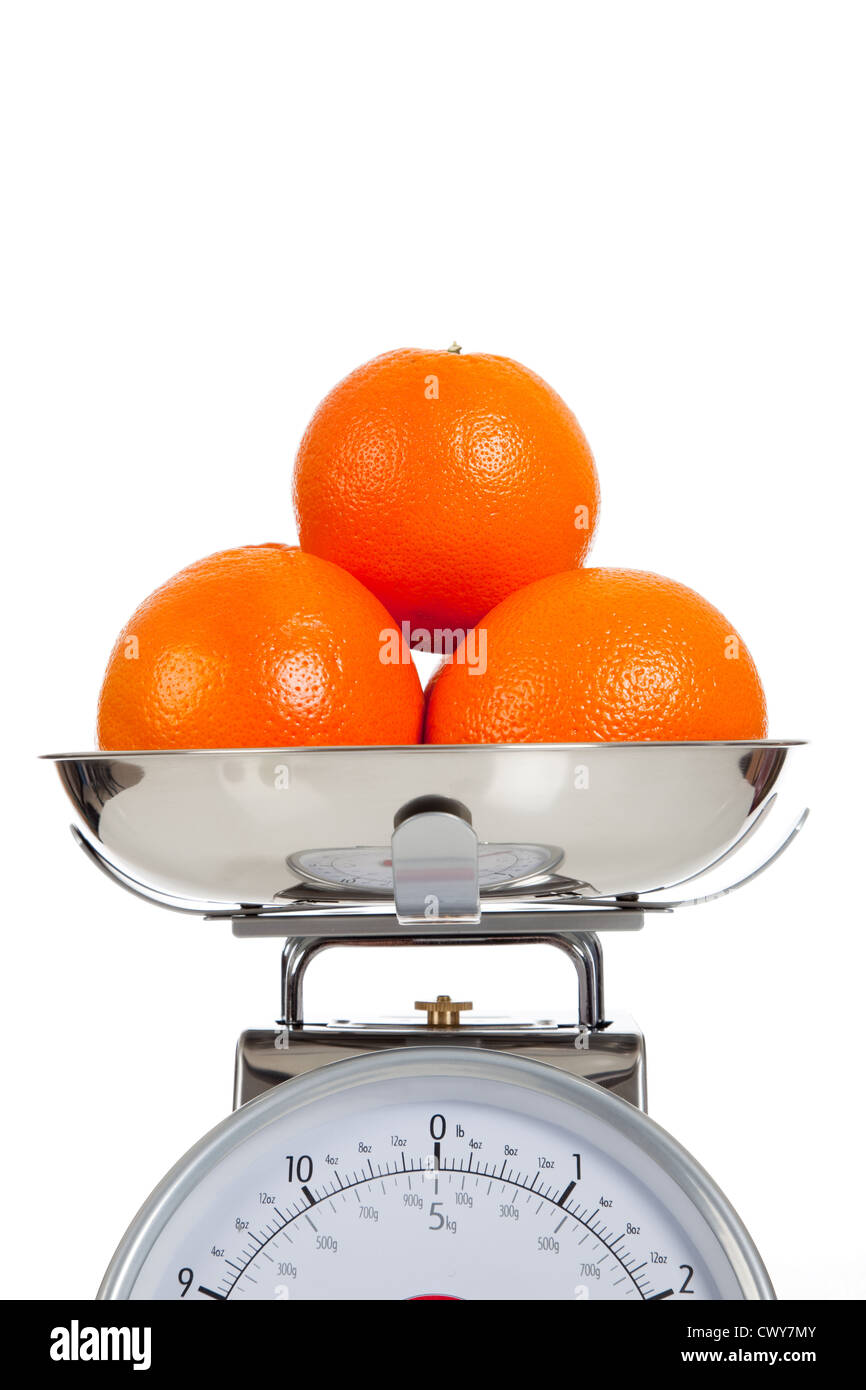 Oranges on a food scale with a white background - Stock Image