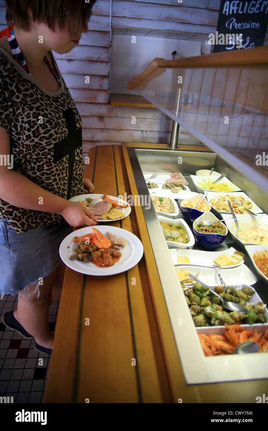 Person choosing food from a buffet. - Stock Image
