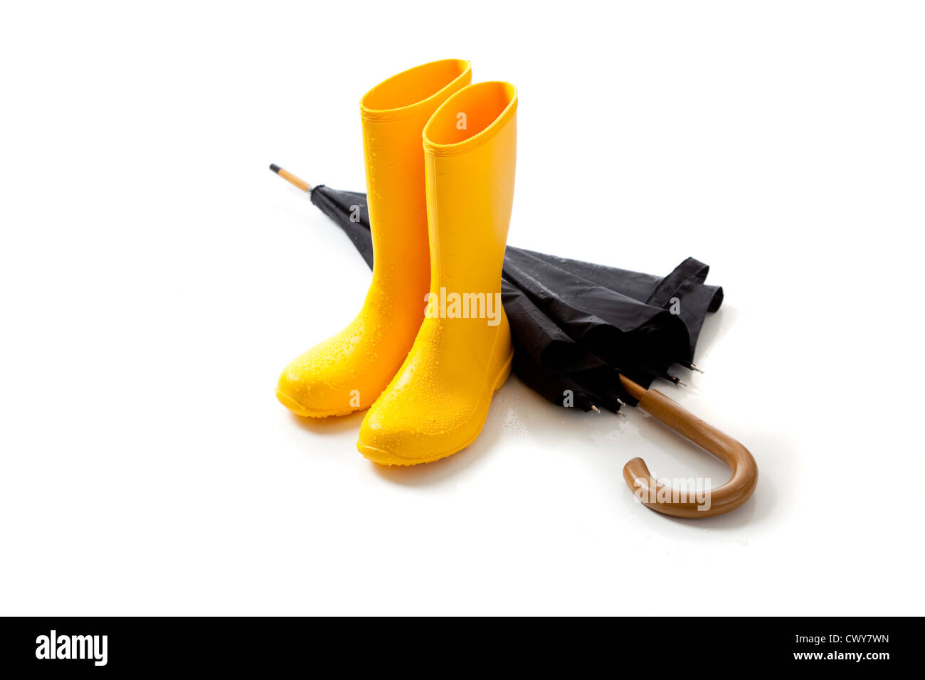 A pair of yellow rain boots and a black umbrella on a white background with copy space - Stock Image