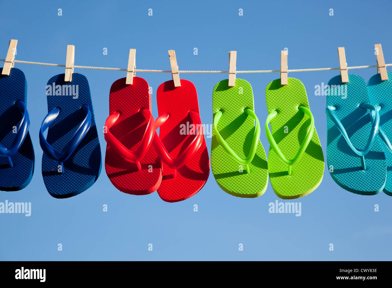 eec0b6788e64e2 Various colored flipflops on a clothesline with a sky blue background