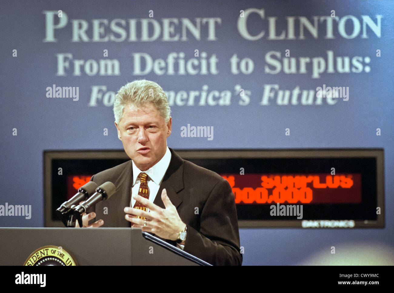 US President Bill Clinton standing in front of the new Budget Surplus Clock announces the first federal budget surplus - Stock Image