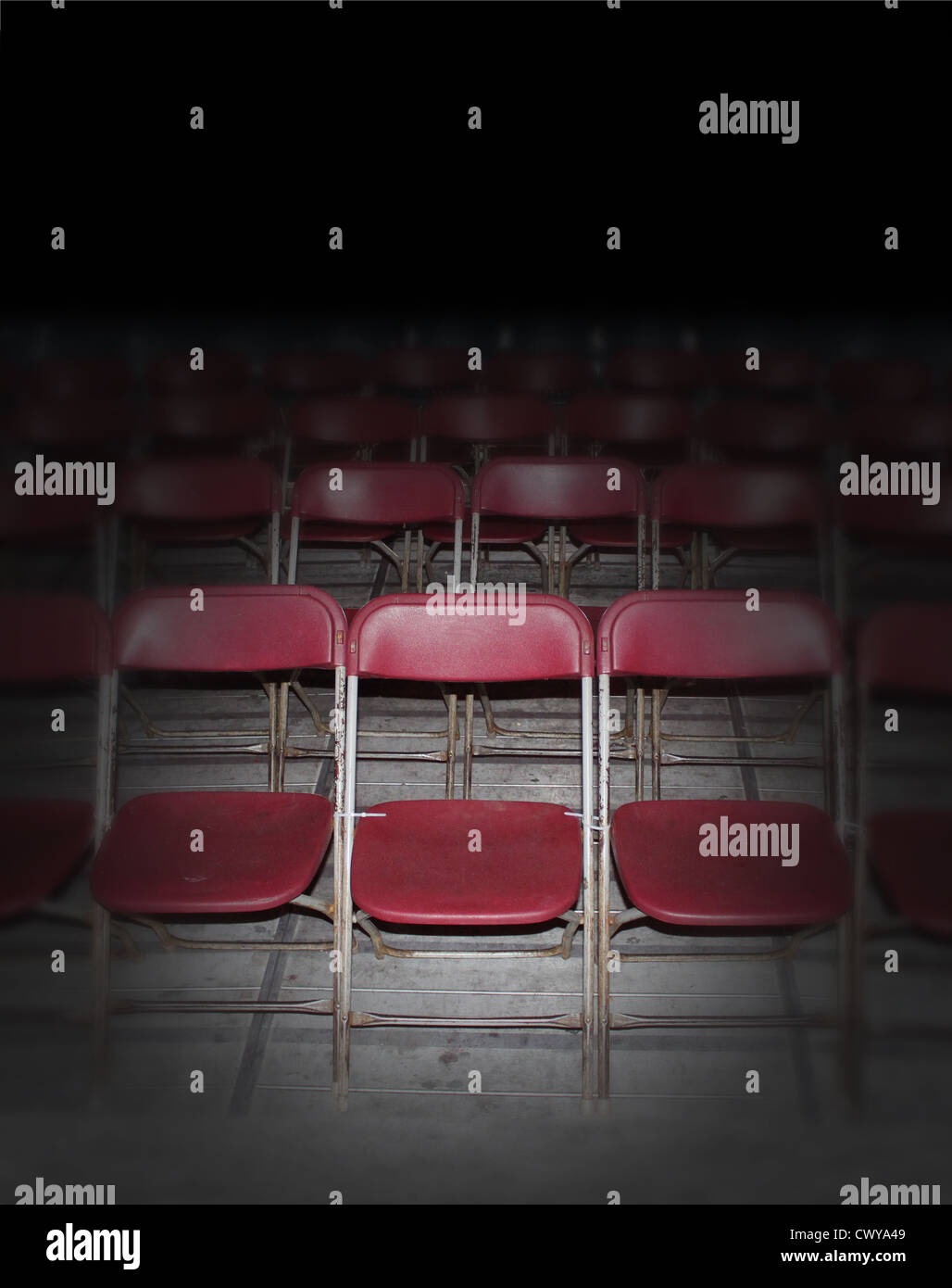 Empty red seating in an auditorium or town hall meeting with rows of old rusting folding chairs in perspective as - Stock Image