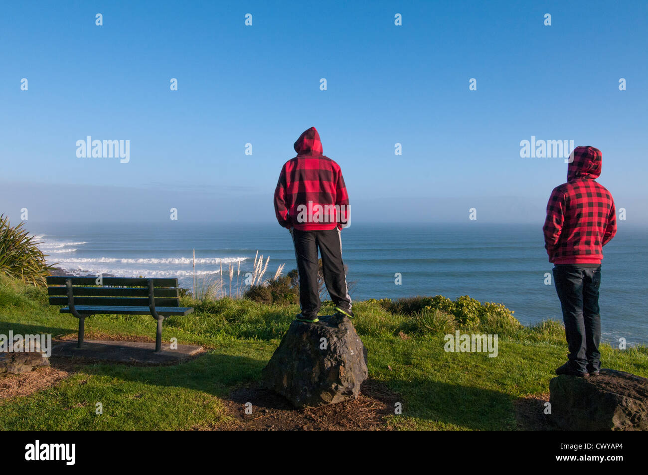 Two men watching the surf from cliff overlooking Whale Bay, with surf points Whale Bay and Indicators in foreground. - Stock Image