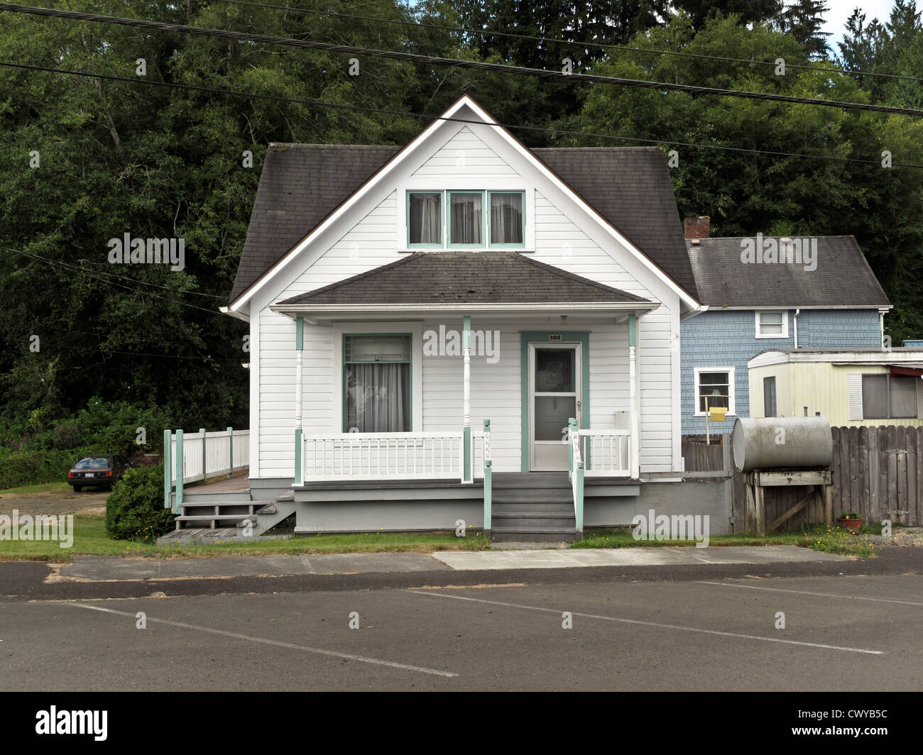 Small Simple White Clapboard Victorian Style House With Blue Trim Front Porch Cross Gable Roof
