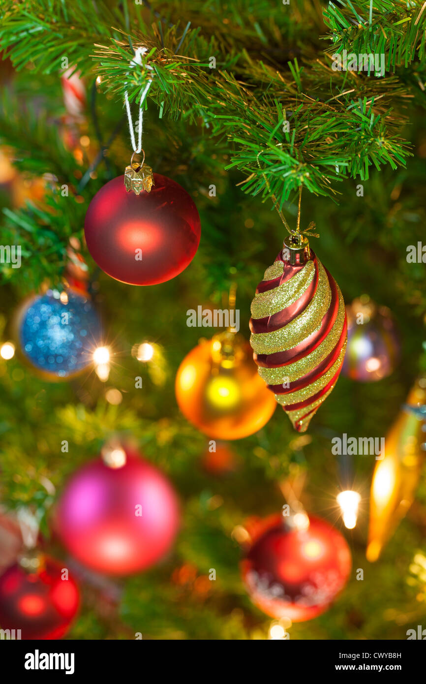 Beautiful traditional christmas decorations on an illuminated xmas tree - Stock Image