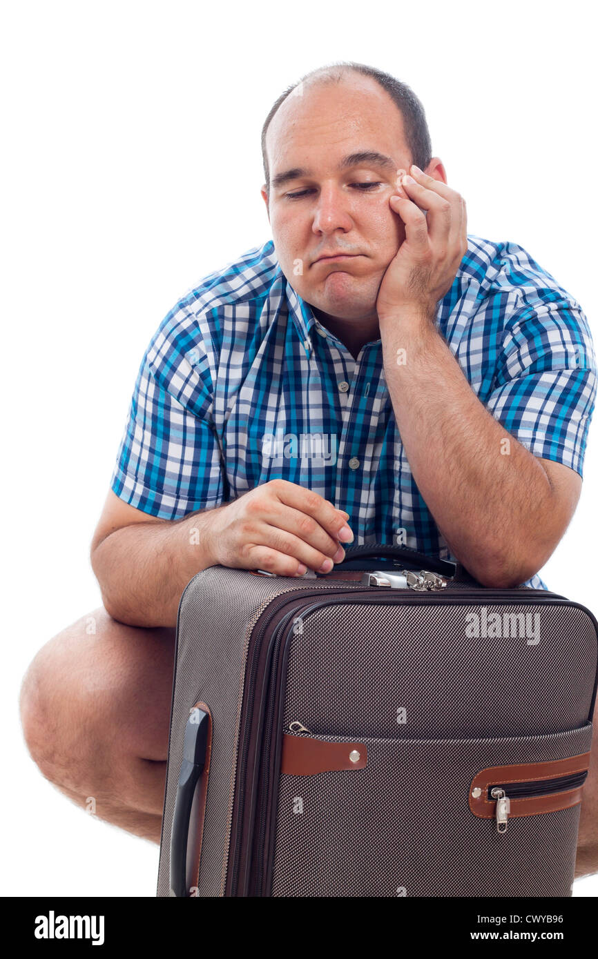 Bored traveller tourist man waiting with luggage, isolated on white background. - Stock Image
