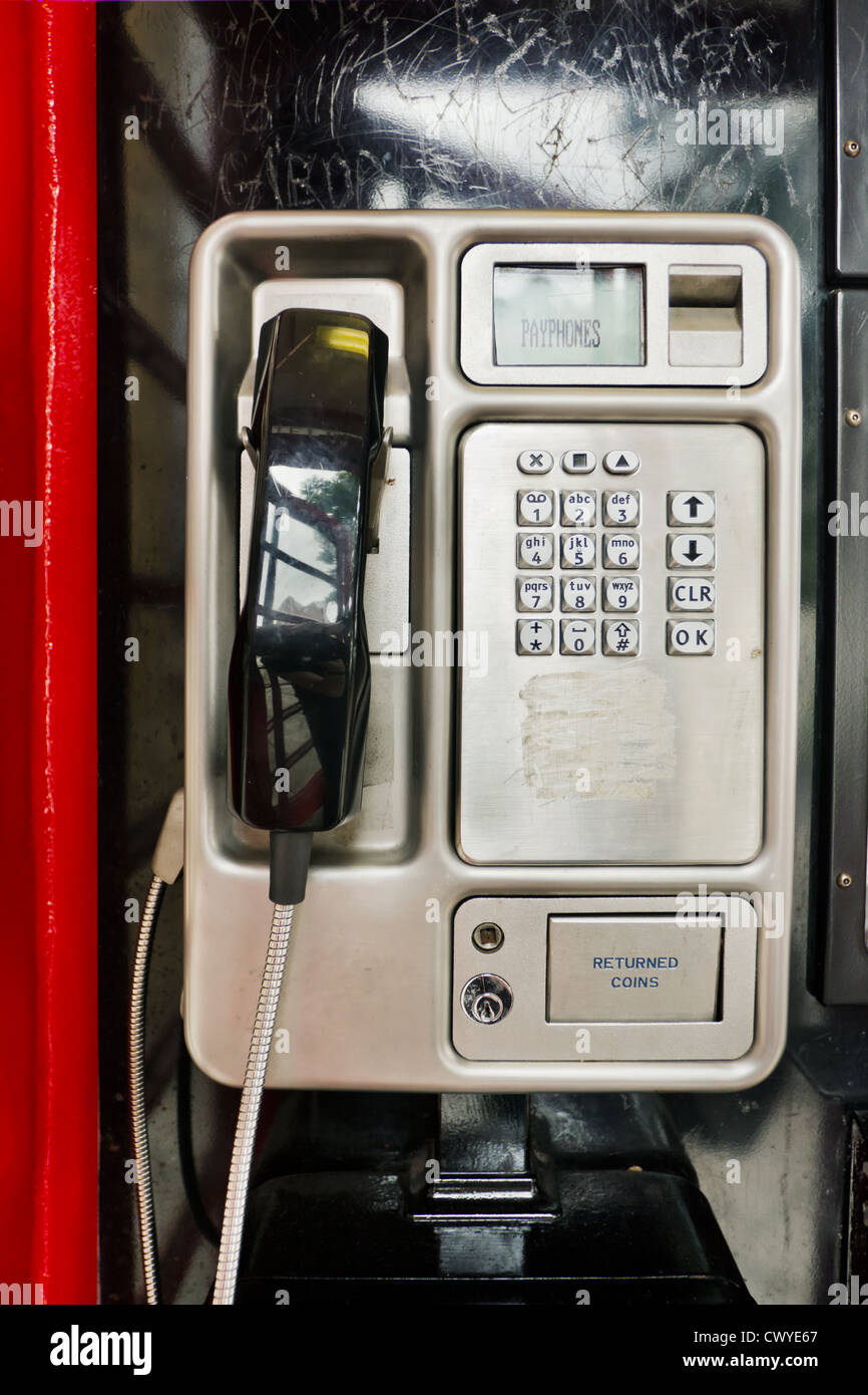 Telephone receiver in a red public phone box - Stock Image