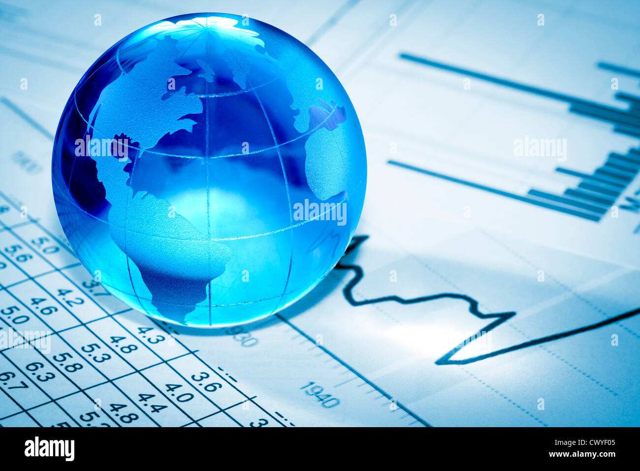 Globe showing North America and resting on financial papers - Stock Image