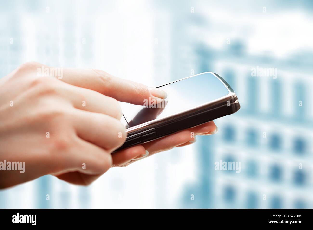 Closeup of female hands using a smart phone. City background. - Stock Image