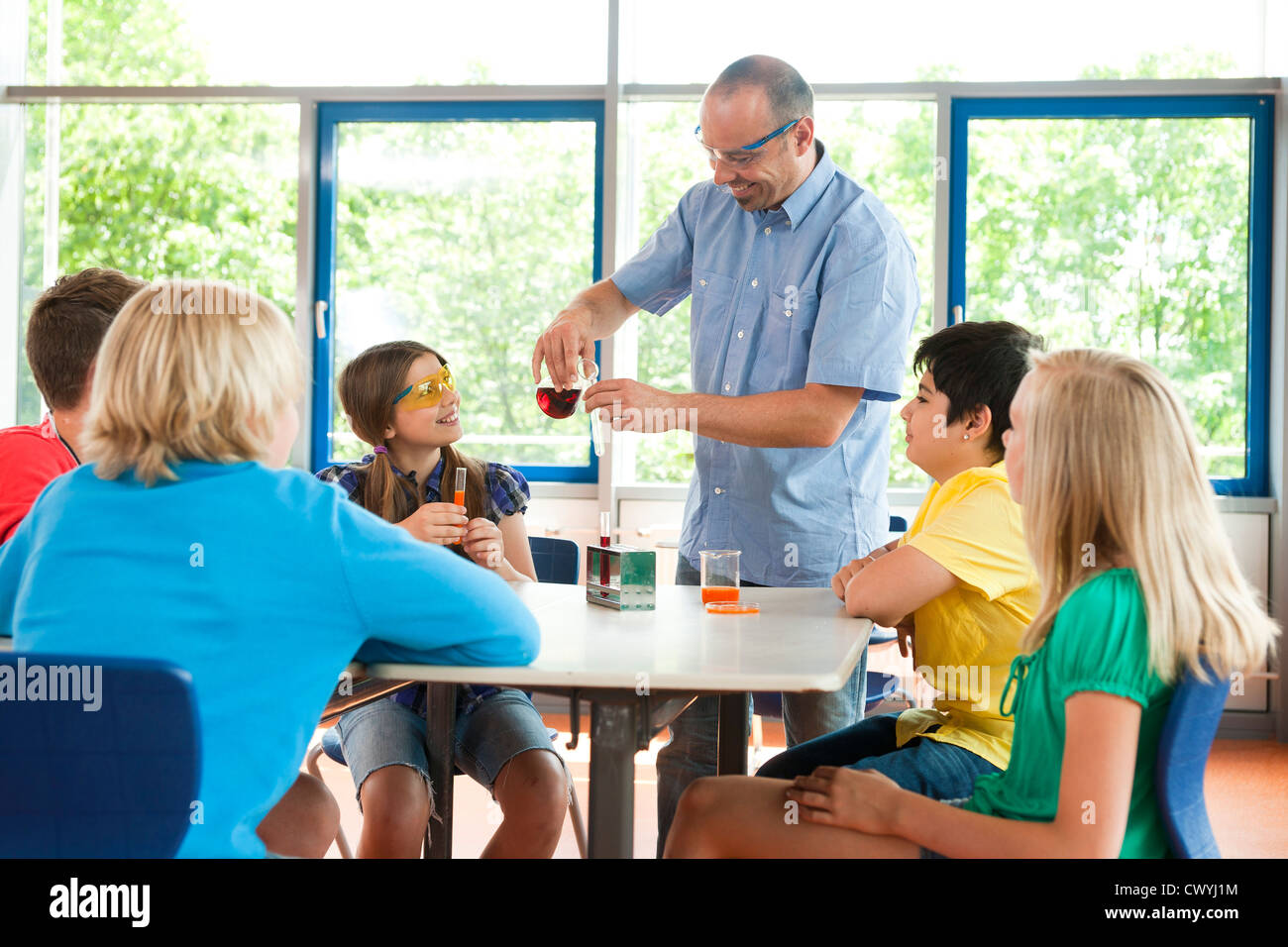 Teacher and pupils experimenting in chemical class - Stock Image