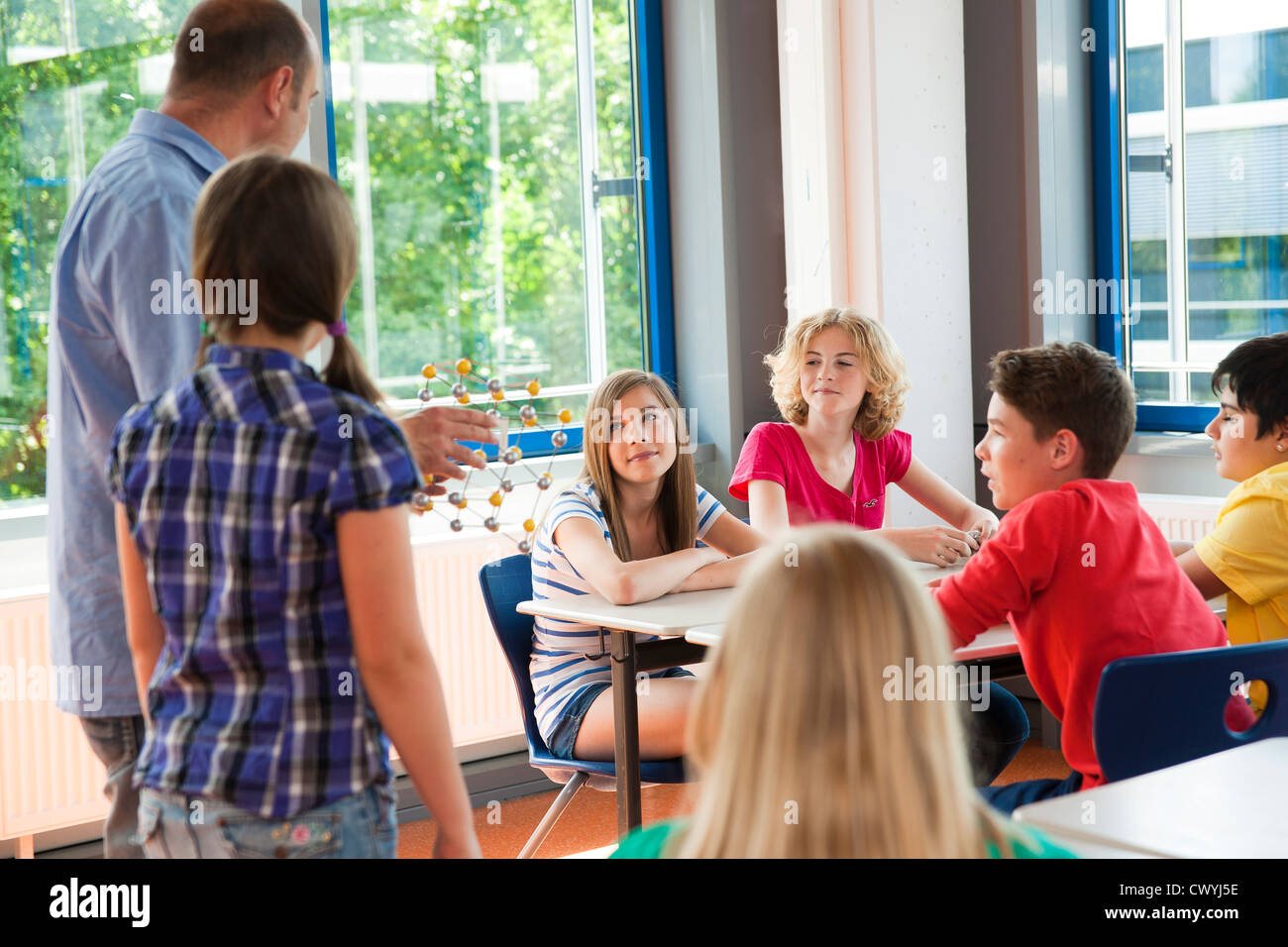 Teacher with molecular model in class - Stock Image
