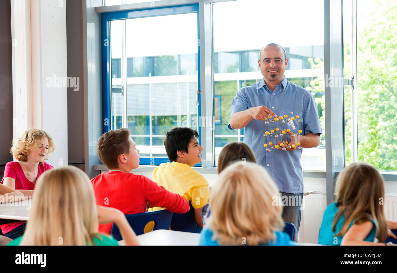 Teacher with molecular model in class Stock Photo