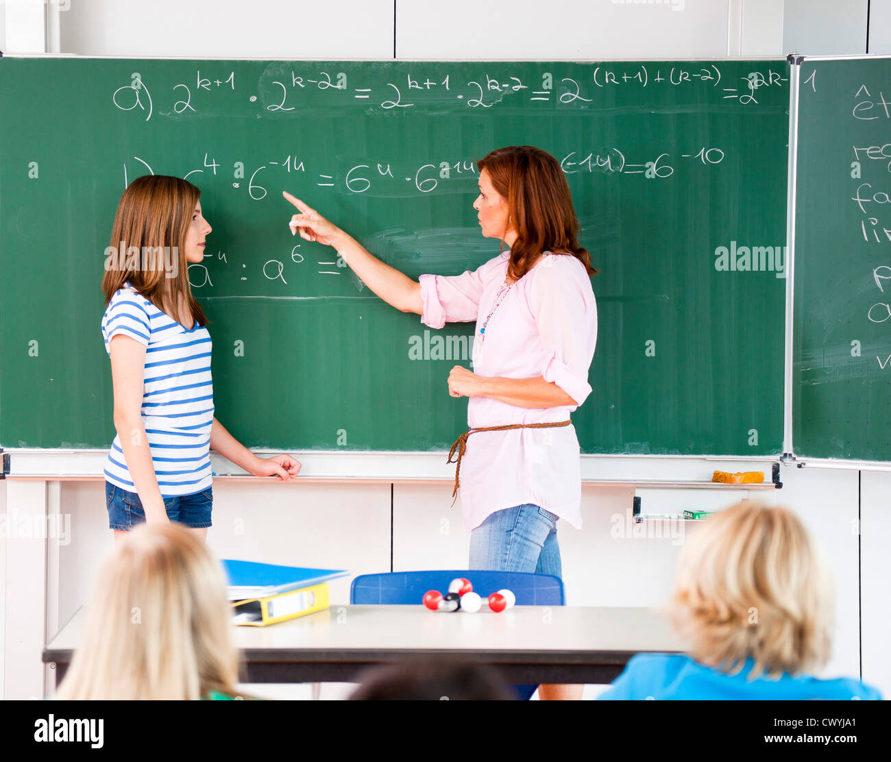 Schoolgirl with teacher at blackboard with formula Stock Photo