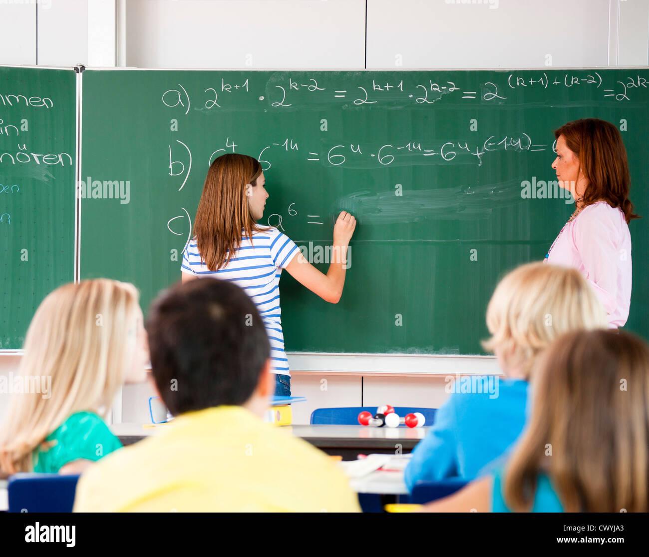 Schoolgirl writing formula at blackboard Stock Photo