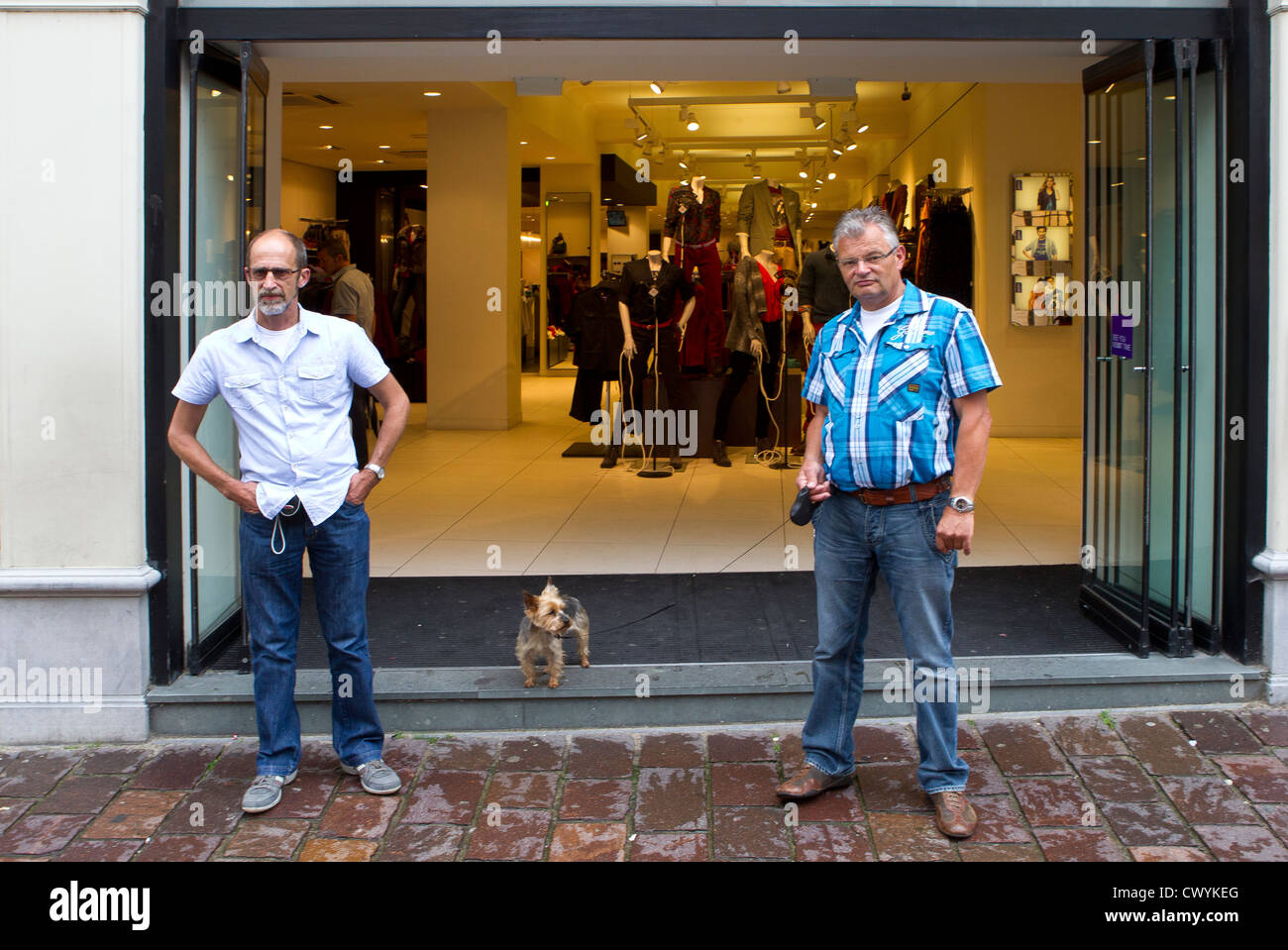 2 two men dog standing doorway shop - Stock Image