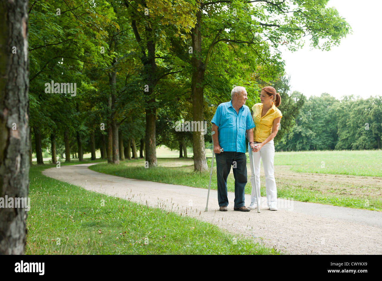 Woman walking with old man in park - Stock Image