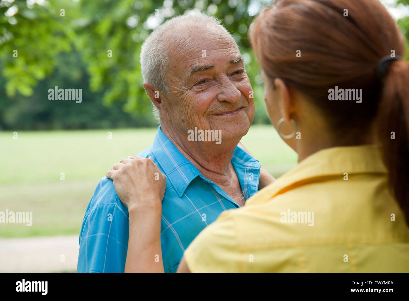 Woman with old man in park - Stock Image