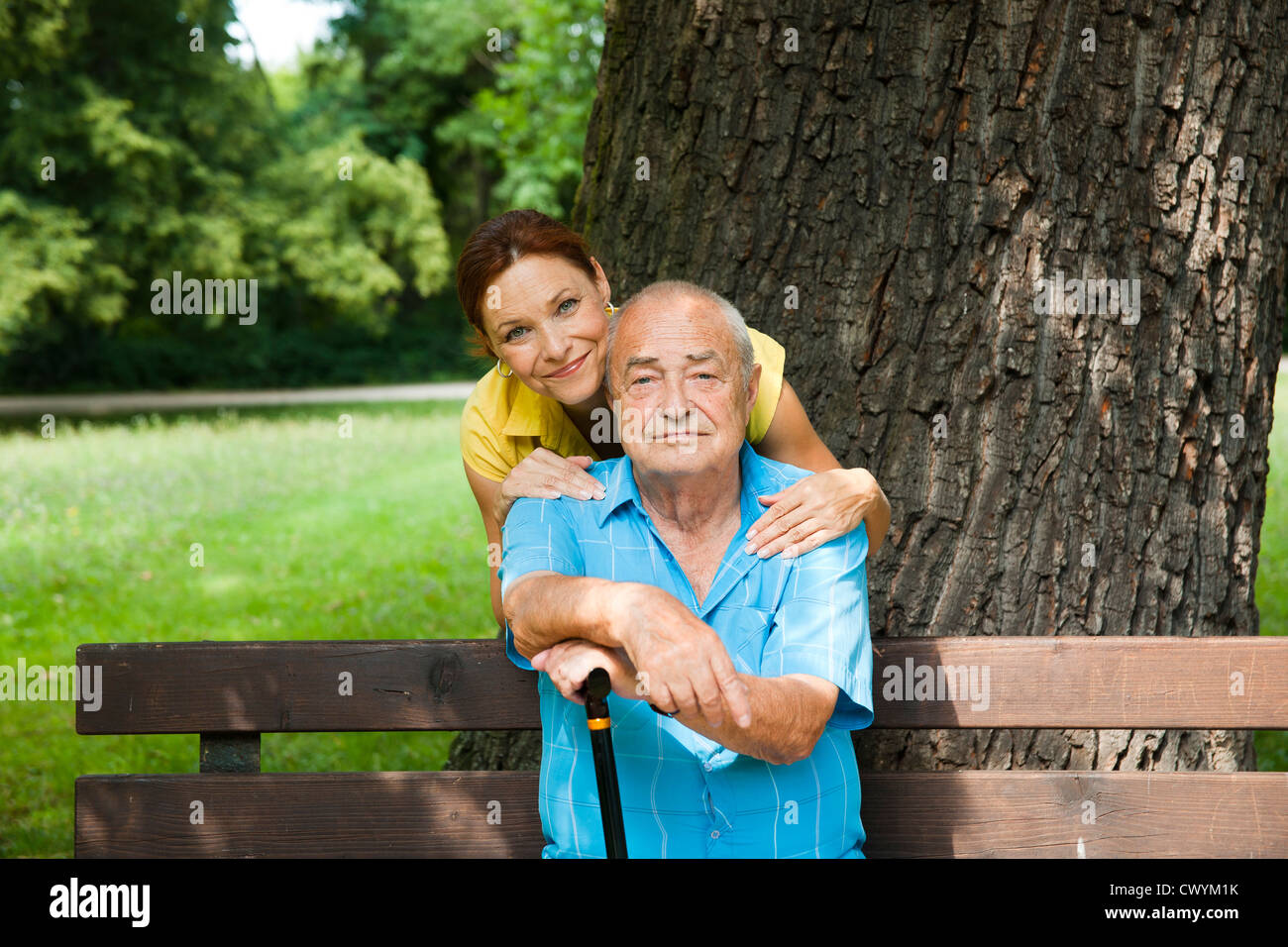Woman with old man on park bench - Stock Image