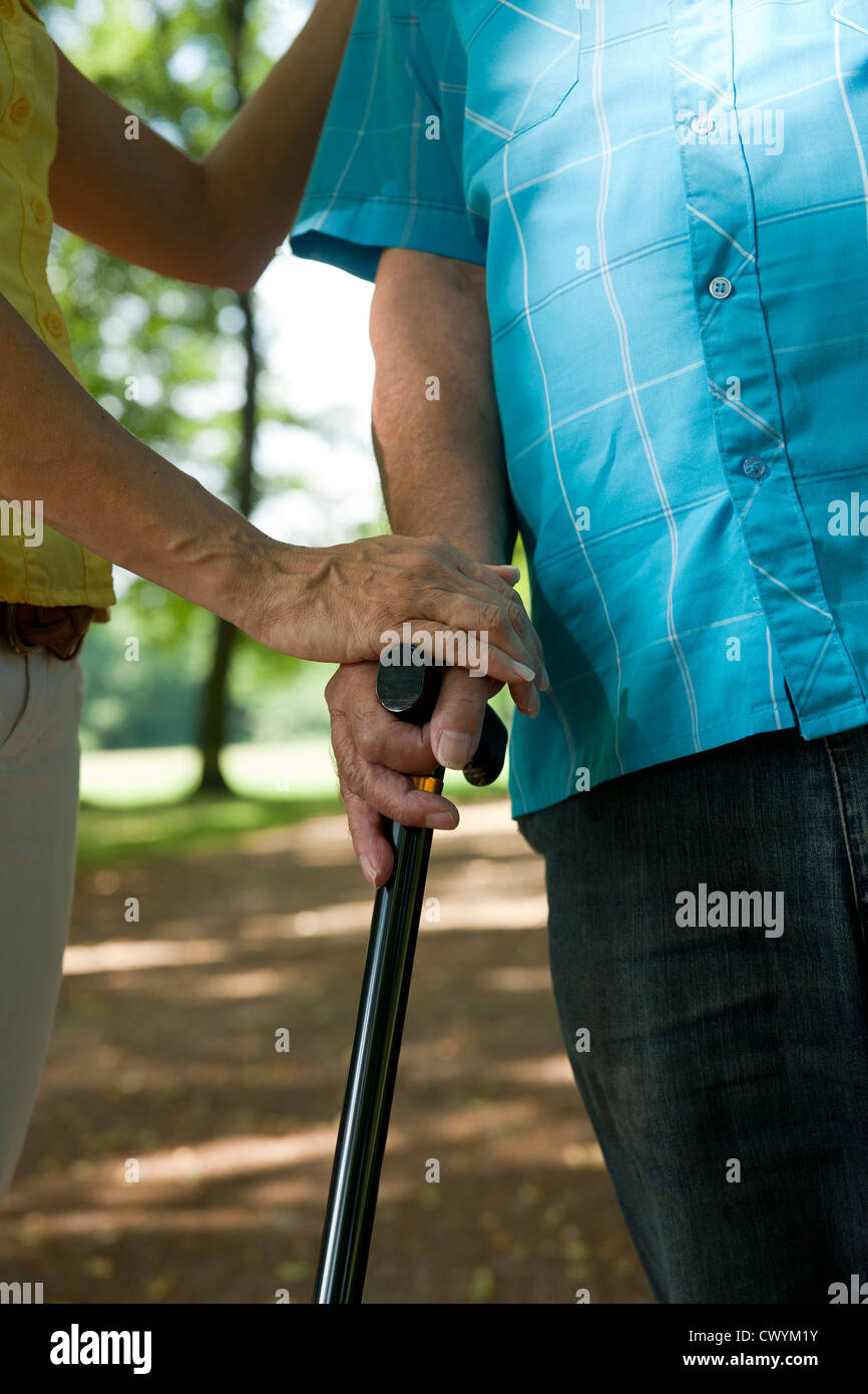 Woman assisting old man in park - Stock Image