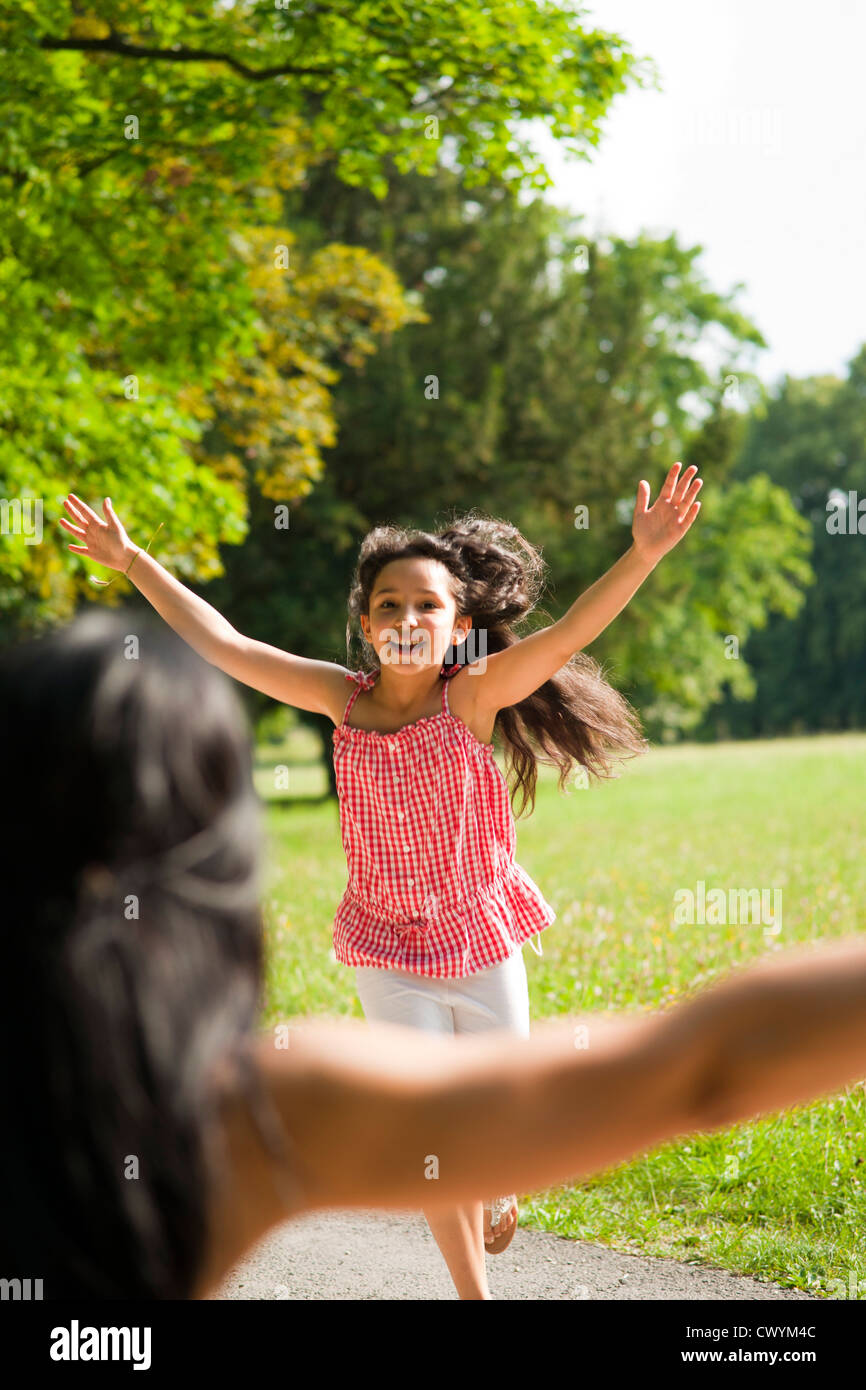 Daughter running towards mother in park - Stock Image