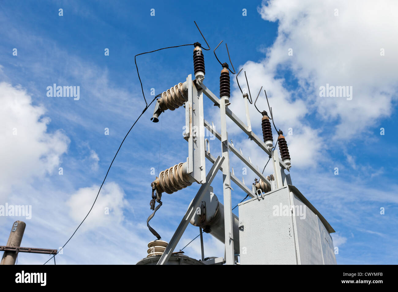 Energy and technology: electrical post by the road with power line cables, - Stock Image