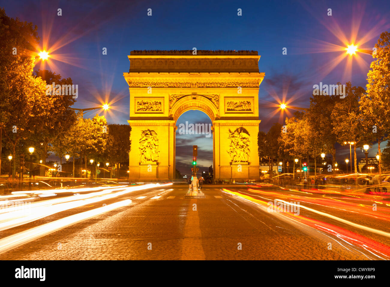 arc du triomphe and Champs Elysees traffic light trails at night Paris France EU Europe - Stock Image
