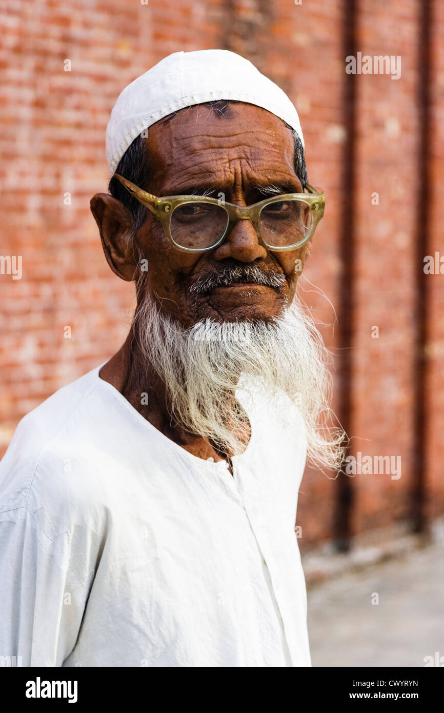 Portrait of old bearded Bangladeshi man by Shait Gumbad Mosque in Bagerhat, Bangladesh - Stock Image