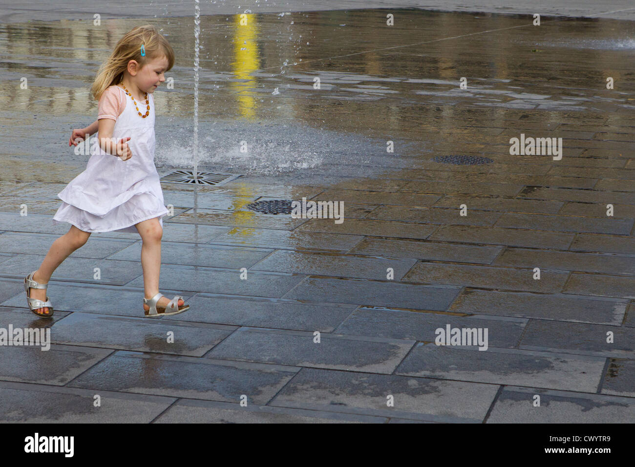 young girl 5 6 7 8 runs running street fountain - Stock Image