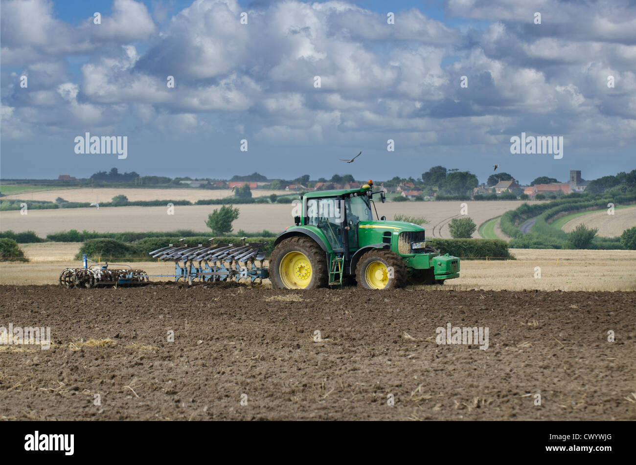 Tractor ploughing with Wighton village and parish church in distance, England - Stock Image