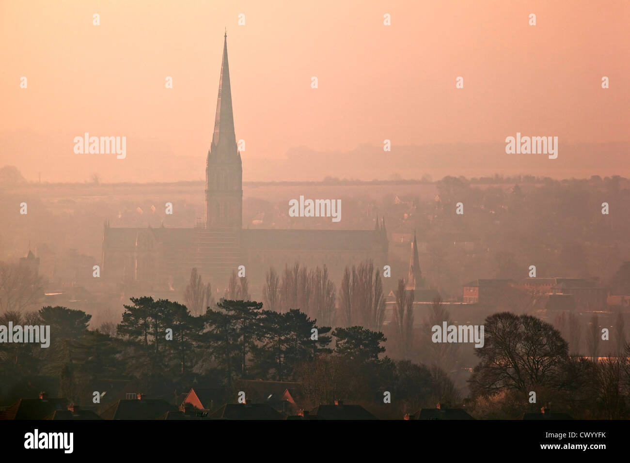 A view of Salisbury Cathedral early in the morning on a misty day, taken from Old Sarum Stock Photo