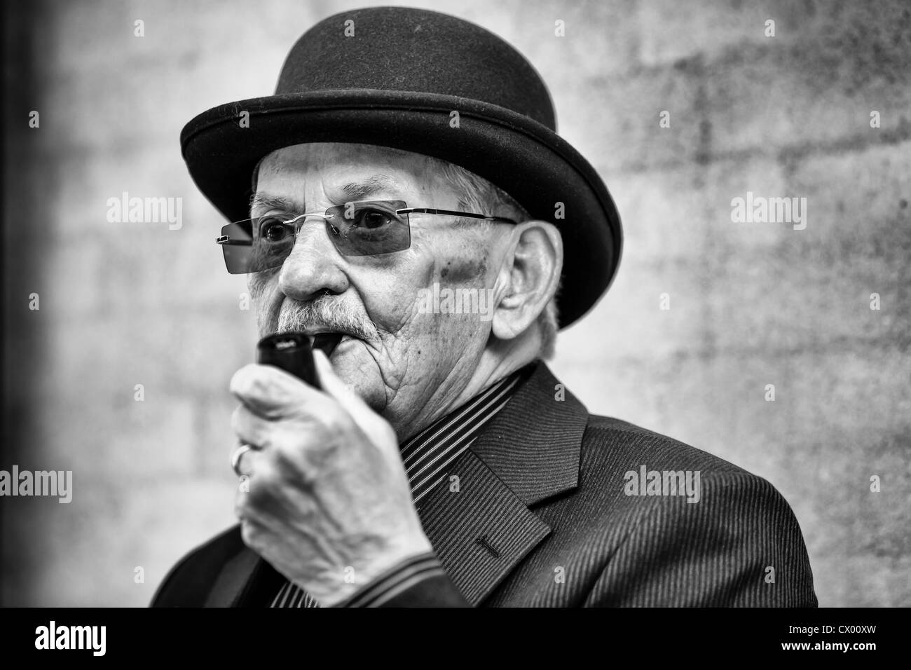 Portrait of elderly Dane with bowler hat ans smoking pipe, Denmark - Stock Image