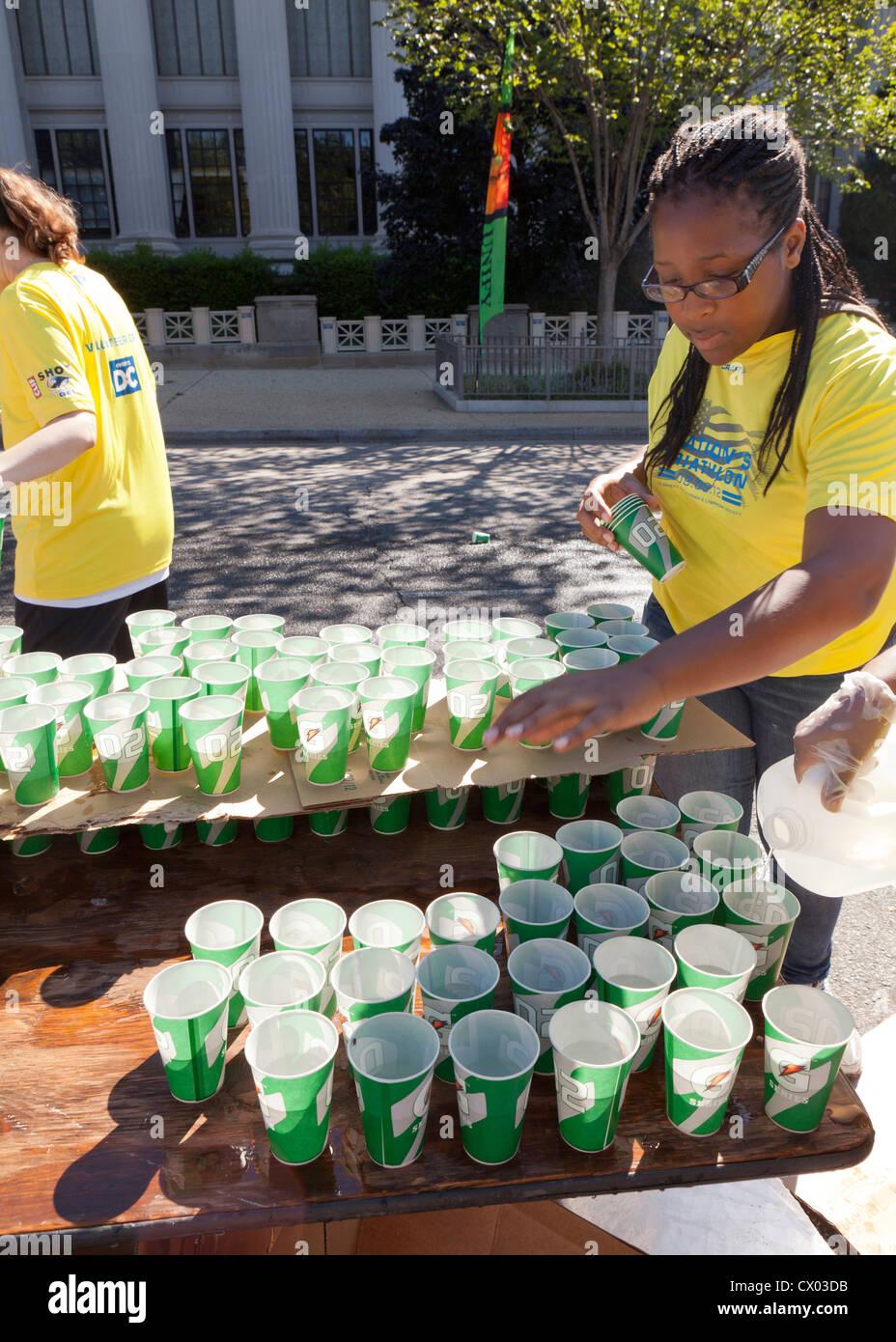 Volunteers preparing water for racers at a marathon - Stock Image