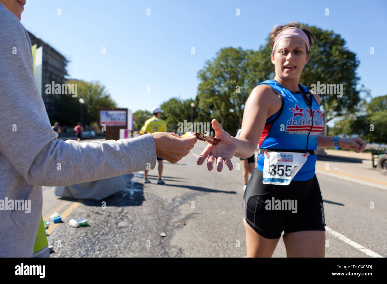 Marathon runner reaching for an energy gel packet - USA - Stock Image