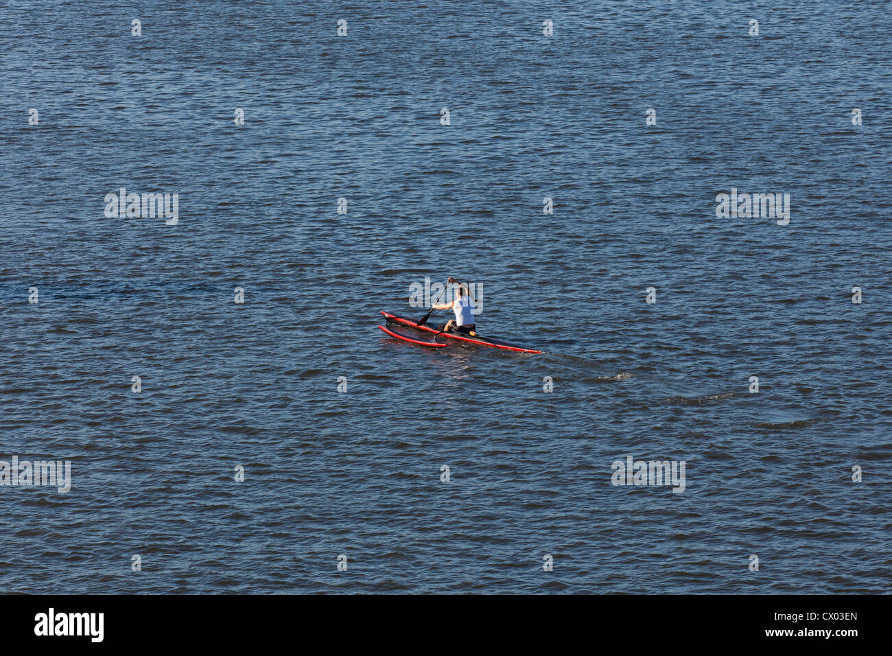 Man on composite kayak with stabilizer - Stock Image